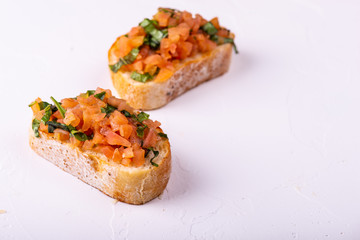 Tasty savory tomato Italian appetizers, or bruschetta, on slices of toasted baguette garnished with basil.