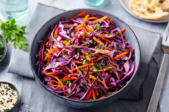 Red cabbage salad. Coleslaw in a bowl. Grey background. Close up.