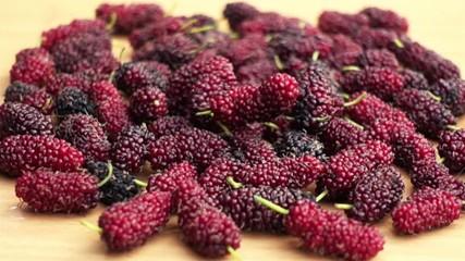 Fototapete - Ripe mulberries fall on a wooden board in Slow Motion