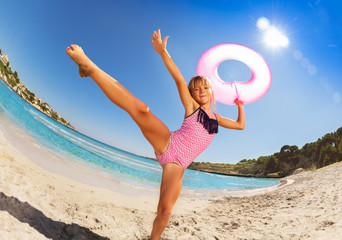 Happy girl dancing with rubber ring on sandy beach Wall mural