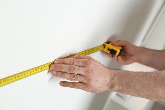 Man measuring white wall indoors, closeup. Construction tool