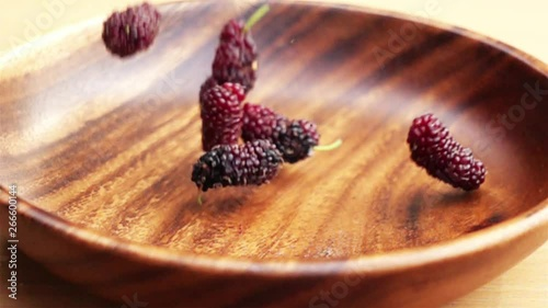 Fototapete Fresh mulberries fall into a wooden bowl on a wooden board in Slow Motion