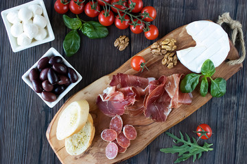 Prosciutto, bread, olives, walnut, salami, basil and cherry tomatoes on  brown wooden board.  Mediterranean kitchen.