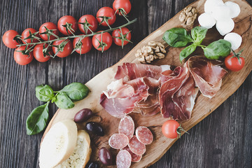 Prosciutto, bread, olives, walnut, salami, basil and cherry tomatoes on  brown wooden board.  Mediterranean kitchen. Top view.