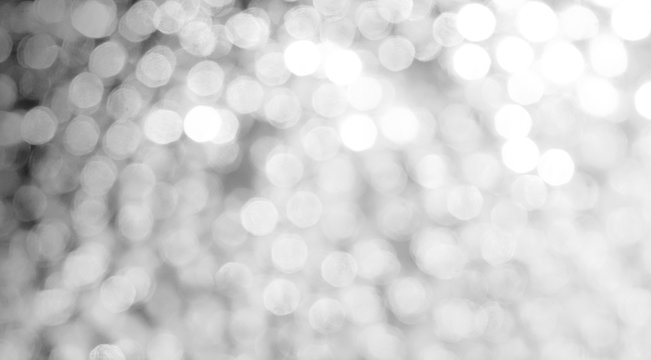 Abstract silver bokeh blurred background with light highlights