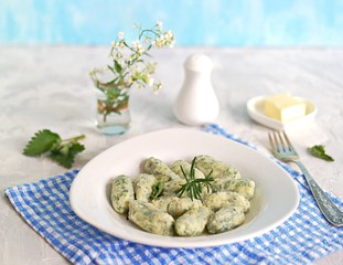 Gnocchi or dumplings with nettle or spinach on a white plate on a light gray background. Served with butter and parmesan cheese. Italian food. Selective focus