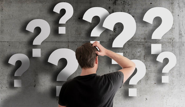 rear view of puzzled man scratching his head against concrete wall filled with question marks