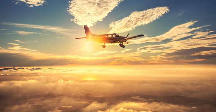 Small single engine airplane flying in the gorgeous sunset sky through the sea of clouds above the spectacular mountains
