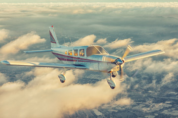 Small single engine airplane flying in the gorgeous sunset sky through the sea of clouds above the spectacular mountains Wall mural