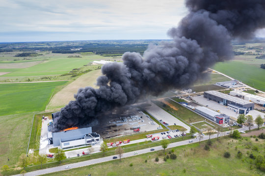 Aerial view of burnt industrial warehouse or logistics center building after big fire with huge smoke from burned roof