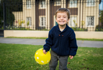 Little boy at his first day of school playing with yellow balloon
