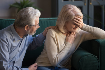 Grey haired husband supporting unhappy mature woman wife at home