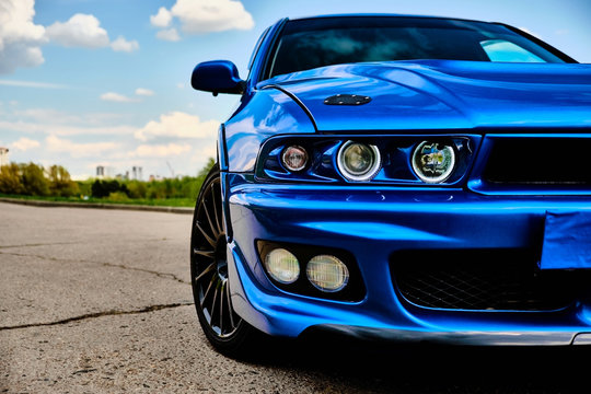 Aggressive sport car in blue against the background of nature