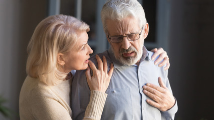 Grey haired man touching chest, having heart attack, woman supporting