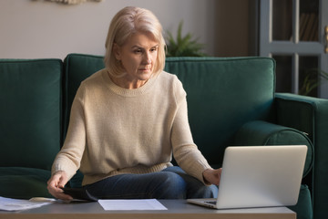 Focused grey haired mature woman calculating bills, using laptop
