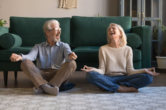 Happy mature couple having fun, practicing yoga together at home