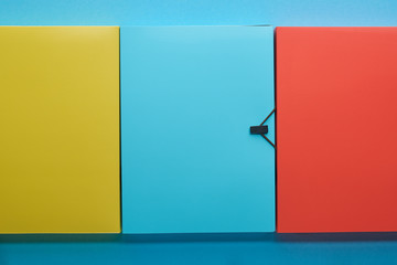 top view of colorful office paper folders on blue