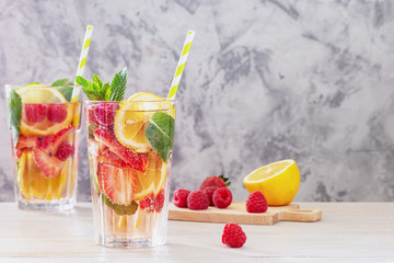 Lemonade with berries and mint. Next to the cutting board are the ingredients. Summer refreshing drink in a tall glass. Light picture with copy space.