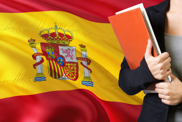 Learning Spanish language concept. Young woman standing with the Spain flag in the background....