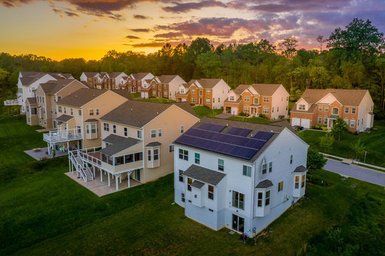 American luxury real estate single family houses with brick facade, solar power roof  and two car garages in a new construction Maryland street neighborhood USA aerial view