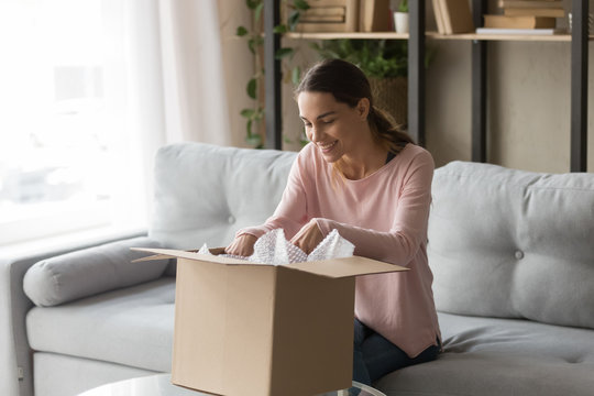 Client woman sitting on couch unbox carton box feels satisfied