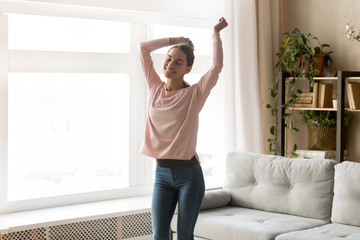 Carefree attractive girl dancing in living room at home Fototapete