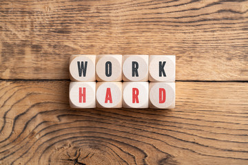 """cubes showing the message """"work hard"""" on wooden background"""