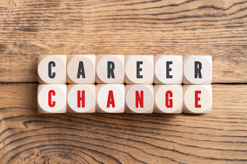 """cubes showing the words """"career"""" and """"change"""" on wooden background"""