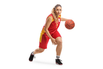 Female basketball player leading a ball