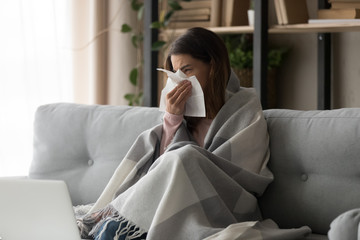 Sick woman covered with plaid blowing nose on paper tissue