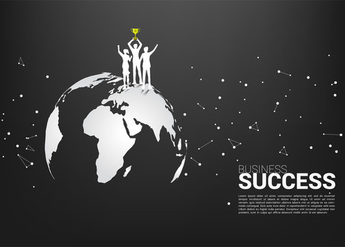 Silhouette of businessman and businesswoman with champion trophy standing on world map. Business Concept of international award winner.