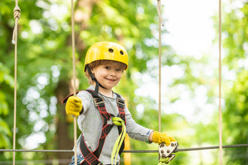 Happy child boy calling while climbing high tree and ropes. Portrait of a beautiful kid on a rope park among trees. Small boy enjoy childhood years.