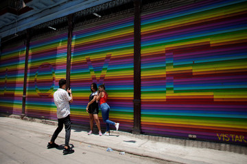 People pose for photos in front of a painting with the colors of the rainbow flag in Havana