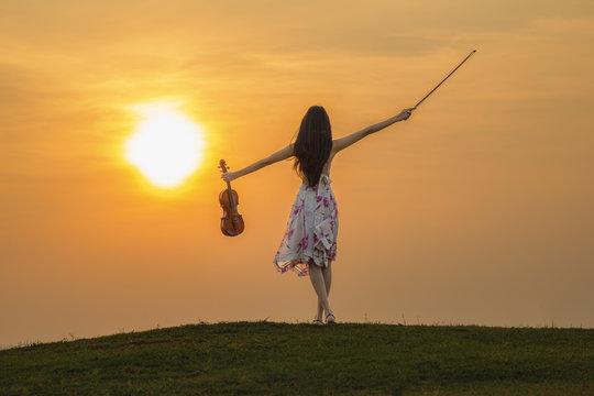 Beautiful woman enjoying music at sunset