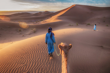 In de dag Marokko Two Tuareg nomads dressed in traditional long blue robes, lead a camel through the dunes of the Sahara Desert at sunrise in Morocco.