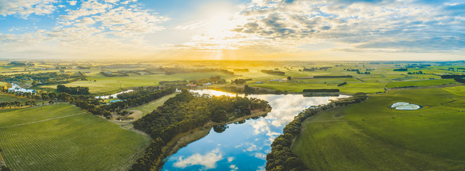 Sun setting over scenic Australian countryside grasslands and pastures with river passing through - aerial panorama Fototapete