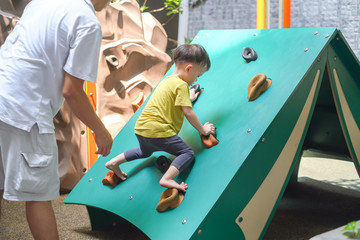 Asian Father & Cute 2 - 3 years old toddler child having fun trying to climb on artificial boulders at playground, Little boy climbing up a rock wall, Hand & Eye Coordination, Motor Skills development