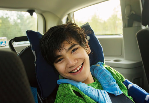 Young disabled boy in wheelchair traveling in handicap vehicle