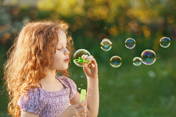 Little girl blowing soap bubbles in spring outdoors.