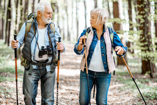 Beautiful senior couple hiking with backpacks and trekking sticks in the forest. Concept of an active lifestyle on retirement