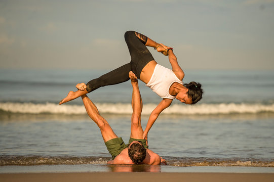 outdoors lifestyle portrait young attractive and concentrated couple of yoga acrobats practicing acroyoga balance and meditation exercise on beautiful beach
