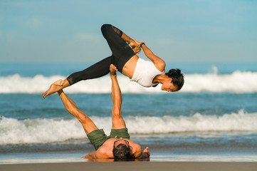 young attractive and concentrated couple of acrobats practicing acro yoga balance and meditation exercise on beautiful beach under a blue sky in mind and body control Wall mural