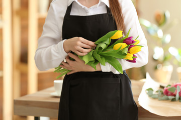 Young florist with bouquet in flower shop