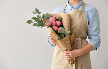 Female florist with bouquet on light background