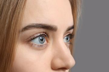 Beautiful young woman with laminated eyelashes on grey background, closeup