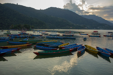 Fotobehang Nepal wooden old empty colorful boats on the lake Phewa on the background of a mountain valley in the fog and the evening sky