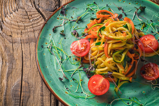 Vegetable pasta from carrot and zucchini. Served on a ceramic plate.
