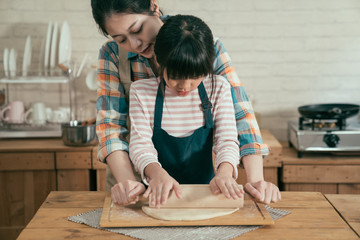 asian mom and daughter using rolling pin together in kitchen kneading dough for happy mothers day homemade cake. woman hugging kid from back teaching baking bread prepared for new year christmas.