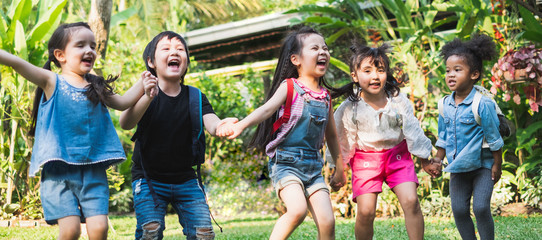 Group of diversity kids holding hands and playing at outdoor park with happy and funny