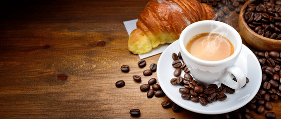 Espresso and croissant with coffee beans on wood background